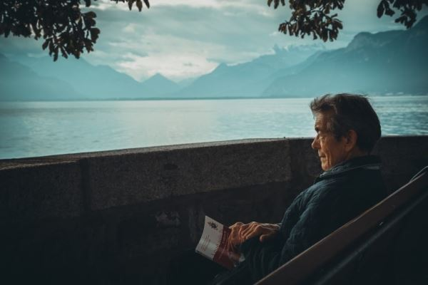 Older Man Sitting by a Lake with a Book